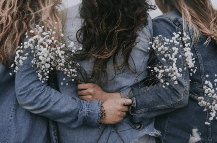 Three women with arms around each other