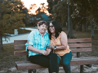 two women sitting on a bench smiling