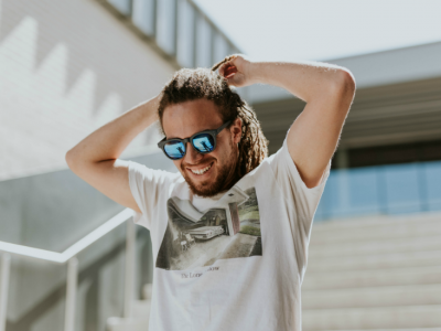 man smiling outside with sunglasses on
