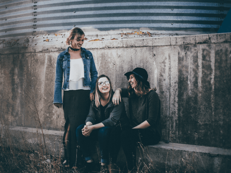 Three young women smiling with each other