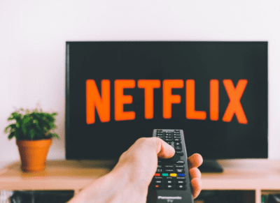 TV remote being pointed at TV with Netflix logo on the screen