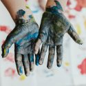 hands with palms up covered in paint
