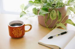 notebook and pen on table with plant and coffee cup