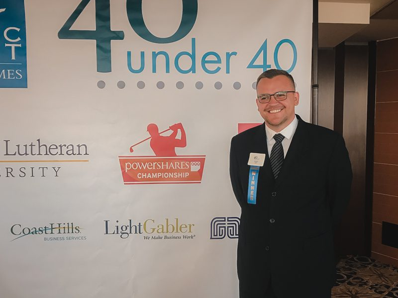 Man in suit standing in front of 40 under 40 poster
