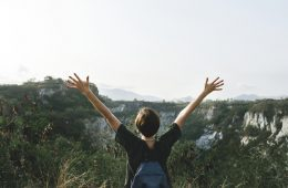 Person raising arms out in nature