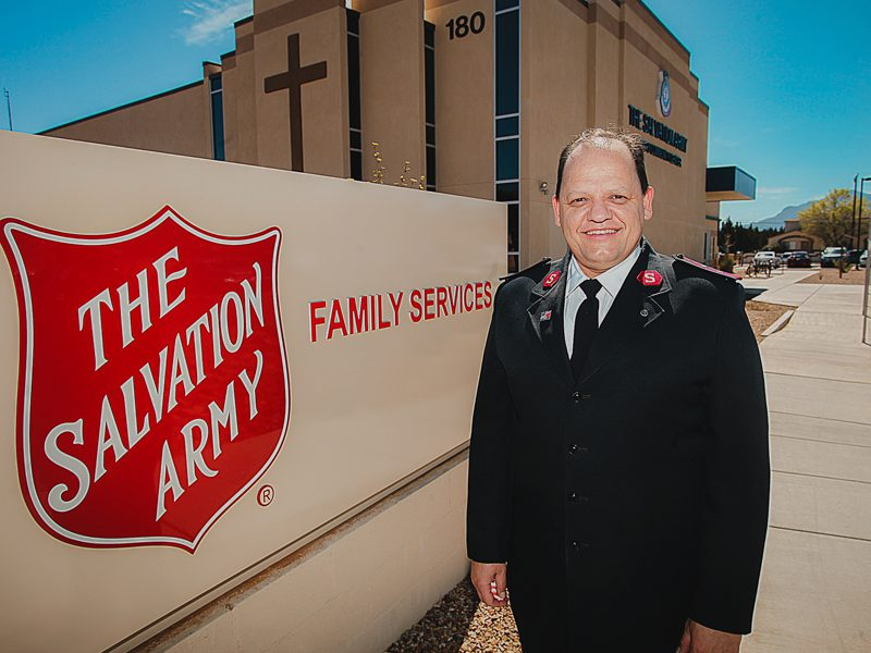 Salvation Army in uniform standing in front of Salvation Army Family Services sign