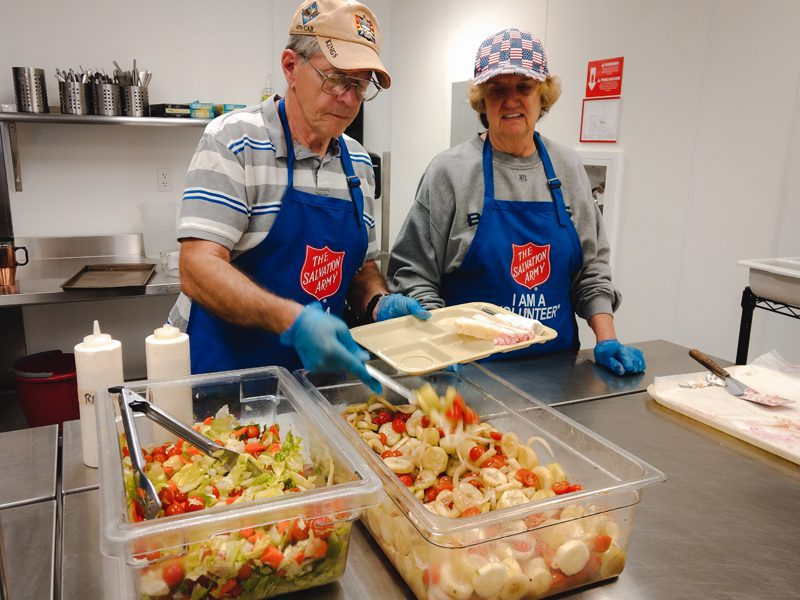Salvation Army volunteers placing food on trays