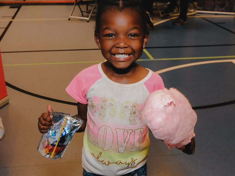 young girl smiling with juice and cotton candy