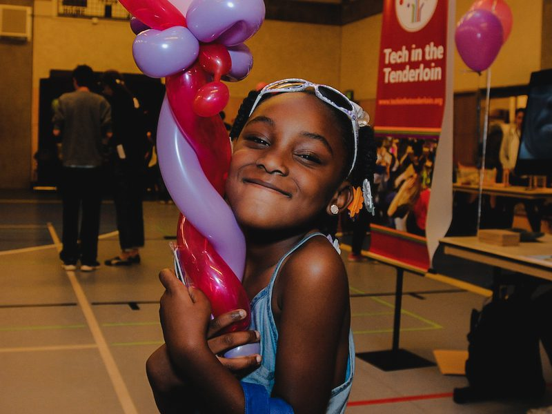 young girl hugs her balloon animal