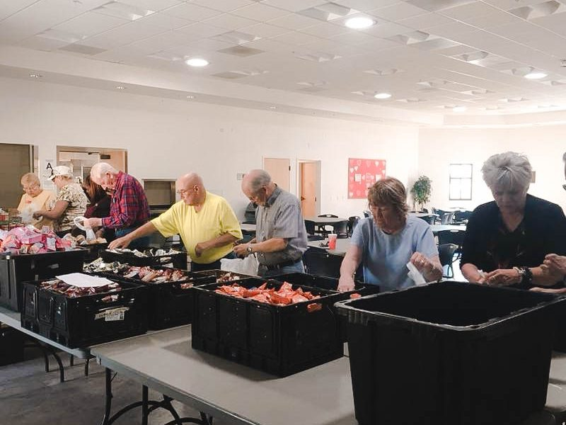 Men and women packing meals