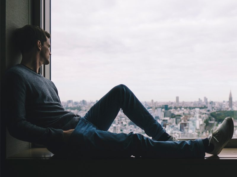 man sitting on ledge looking out at city