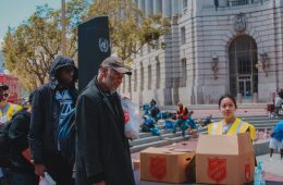Men in line in front of Salvation Army boxes