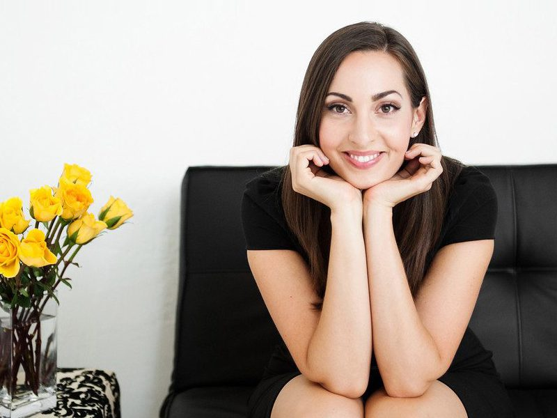 Woman sitting on couch next to flowers