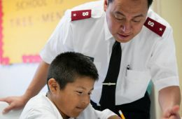 Salvation Army soldier helping child doing homework