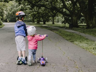 young boy and girl on scooters