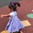 toddler in purple dress playing