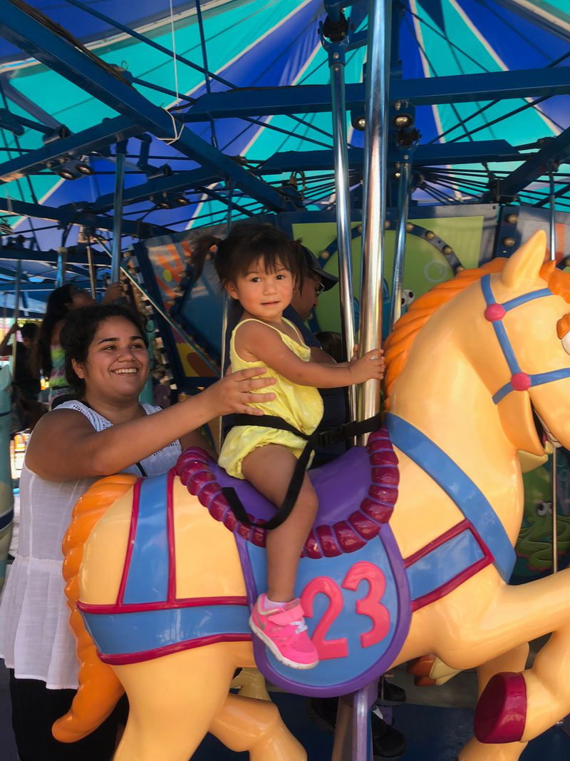 mother supporting daughter on merry-go-round