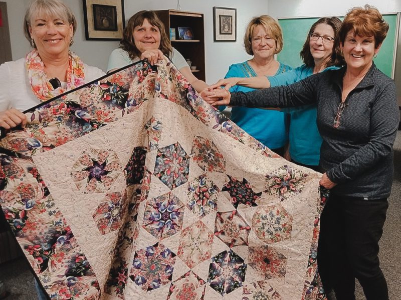 Five women holding finished quilt