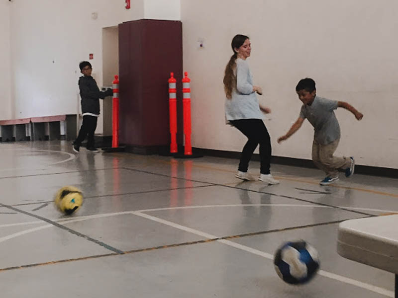 Elizabeth Veras Holland playing soccer with children