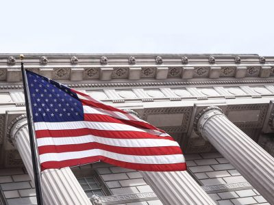 American Flag waving in front of columns