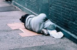 Man in sweatshirt sleeping on cardboard on the street