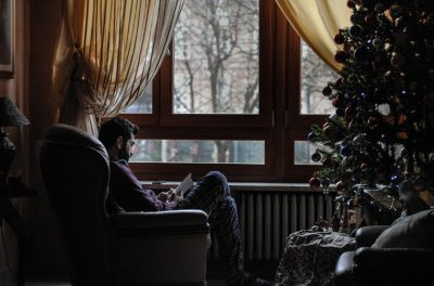 man sitting by window next to Christmas tree