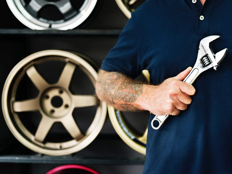 Mechanic with tattoo holding wrench in front of wheels