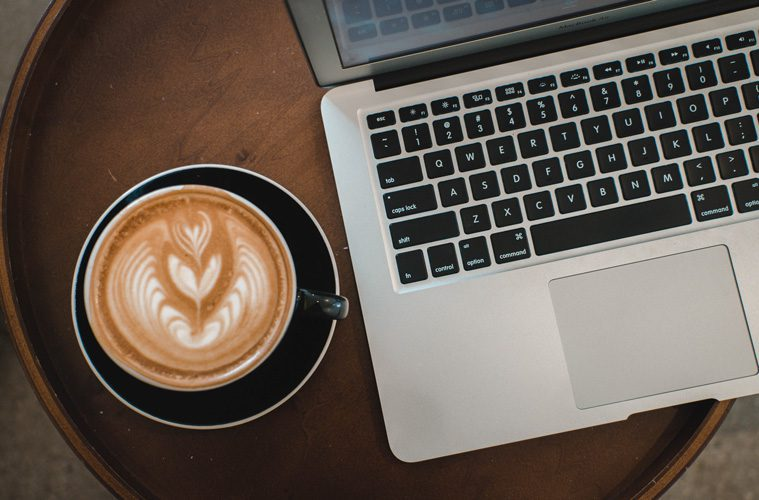 Coffee cup next to laptop
