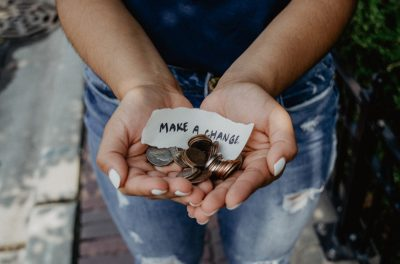 Hands holding change with note that says make a change