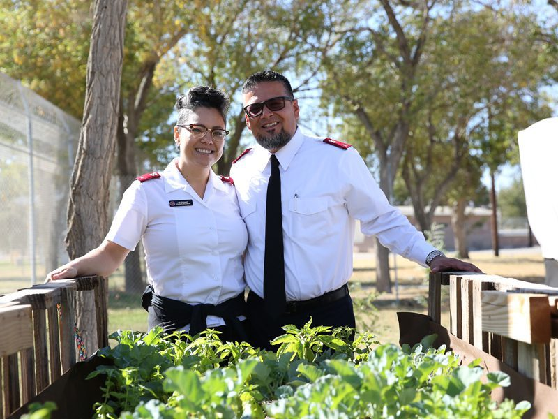 Antelope Valley Officers Hector and Yasmin Acosta smiling in front of plants