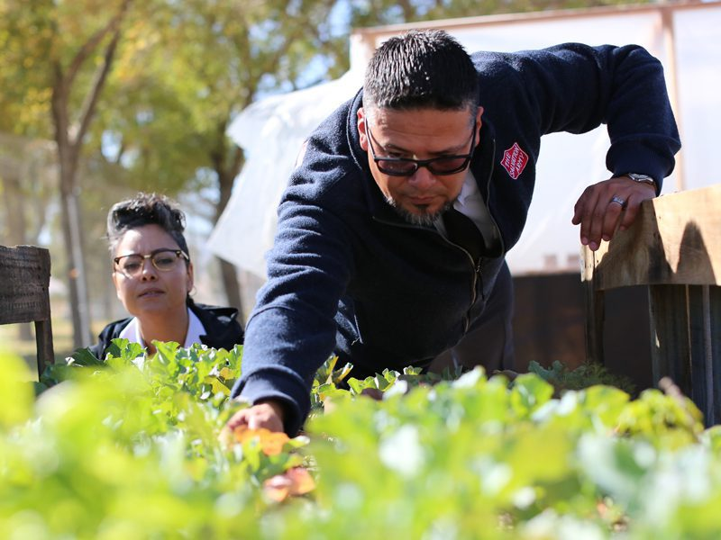 Officers Hector and Yasmin Acosta looking over plants at homeless shelter