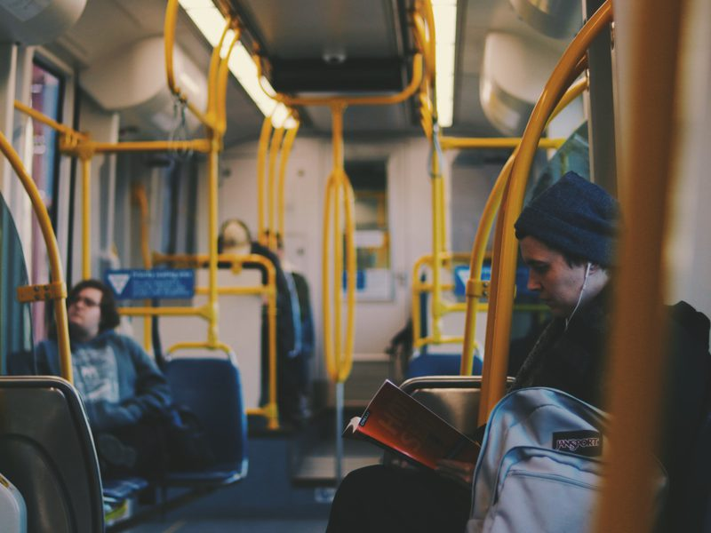 Closeup of man reading on bus with headphones in.