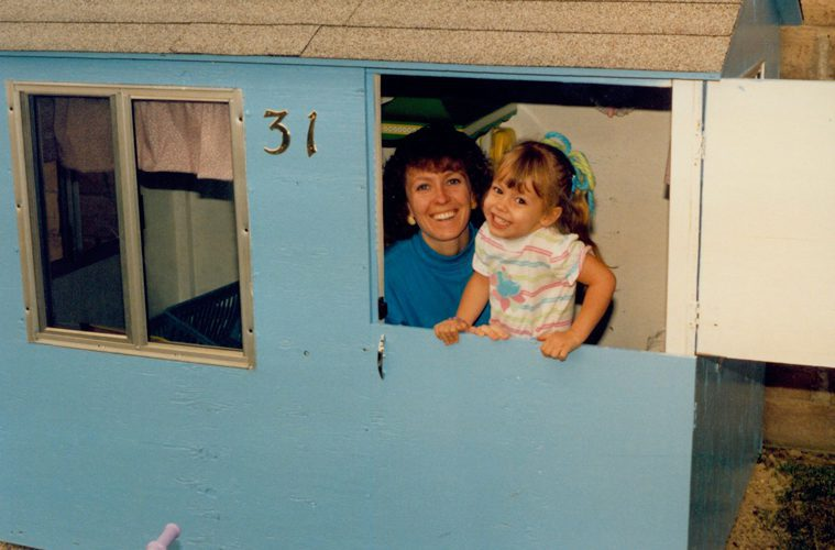 Young Christin with her mom in a blue playhouse