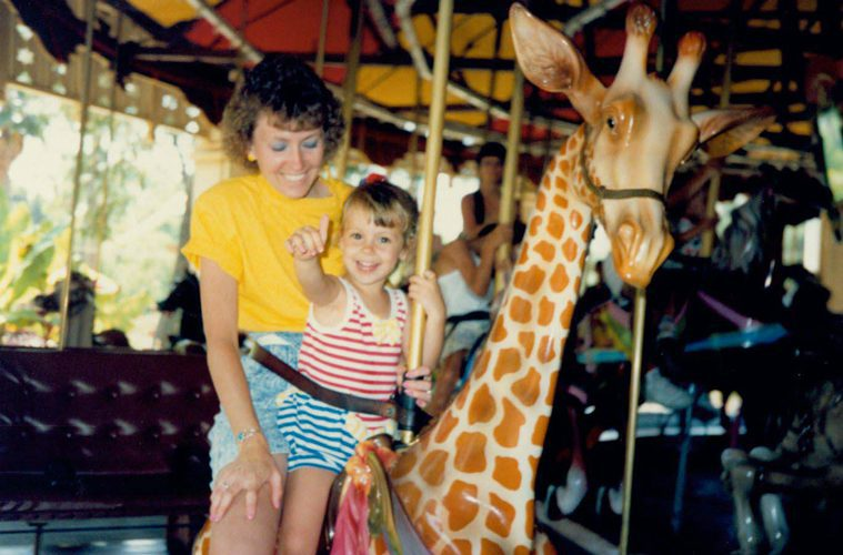 Young Christin and her mom on Carousel giraffe