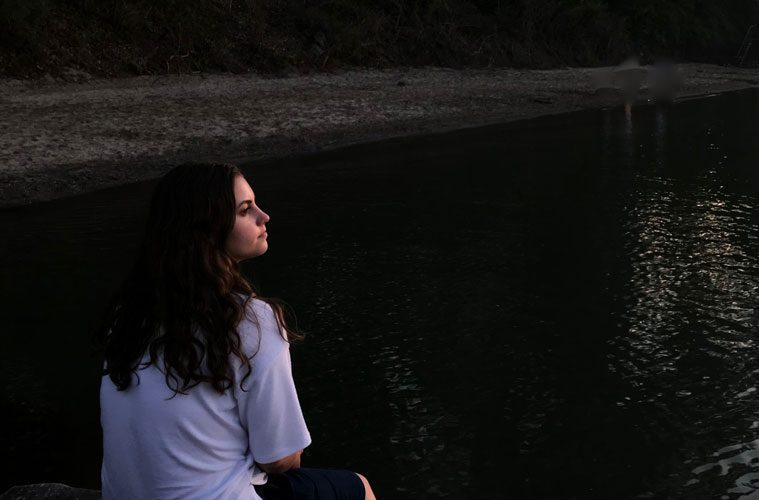 Young Woman Contemplating by Water