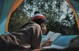 Person Reading Book in Open Tent with Trees in Background