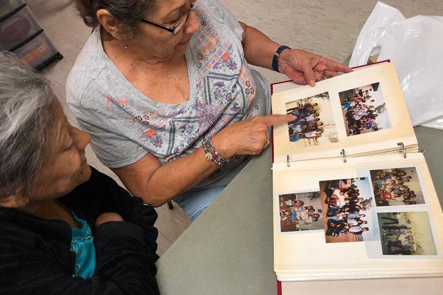 Celia Gonzalez and Maria Botello looking through photo album