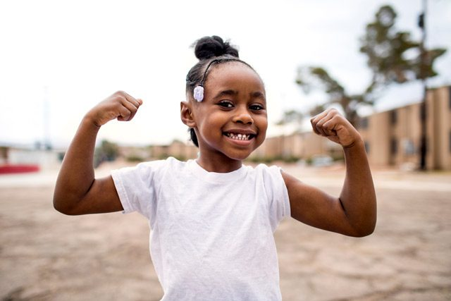 Female child smiling and showing muscles