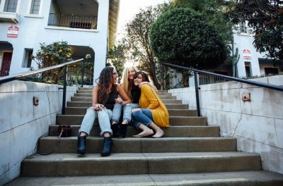 Three female friends laughing together while sitting on stairs