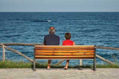 boy and grandpa sitting on bench by water