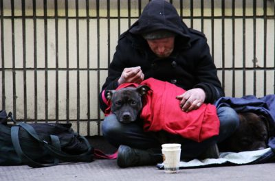 homeless man sitting with dog on lap