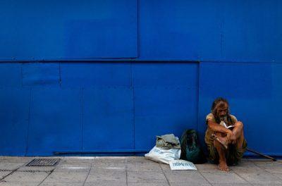 elderly homeless man against blue wall