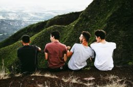 Four Male Friends Sitting on Mountain Ledge Laughing