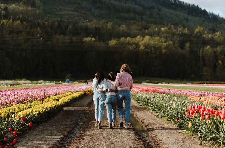 Female Friends with Arms Around Each Other Walking Through Flower Field