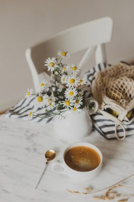 flowers and coffee sitting on table