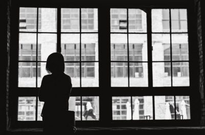 black and white photo of woman looking outside window