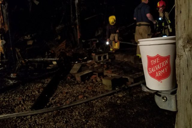 Salvation Army Bucket in Front of Burned Down Area