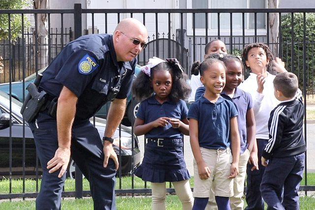 Officer in uniform with children outside