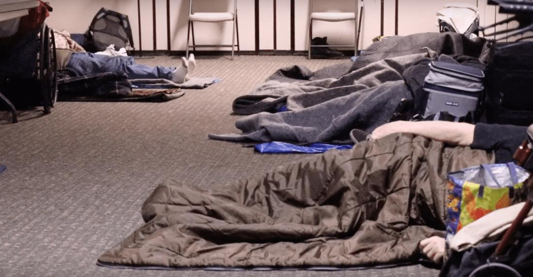 People sleeping in sleeping bags indoors