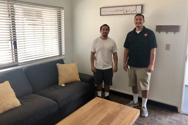 Two men standing next to table and couch